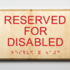 """ADA compliant wooden sign saying """"reserved for disabled"""""""