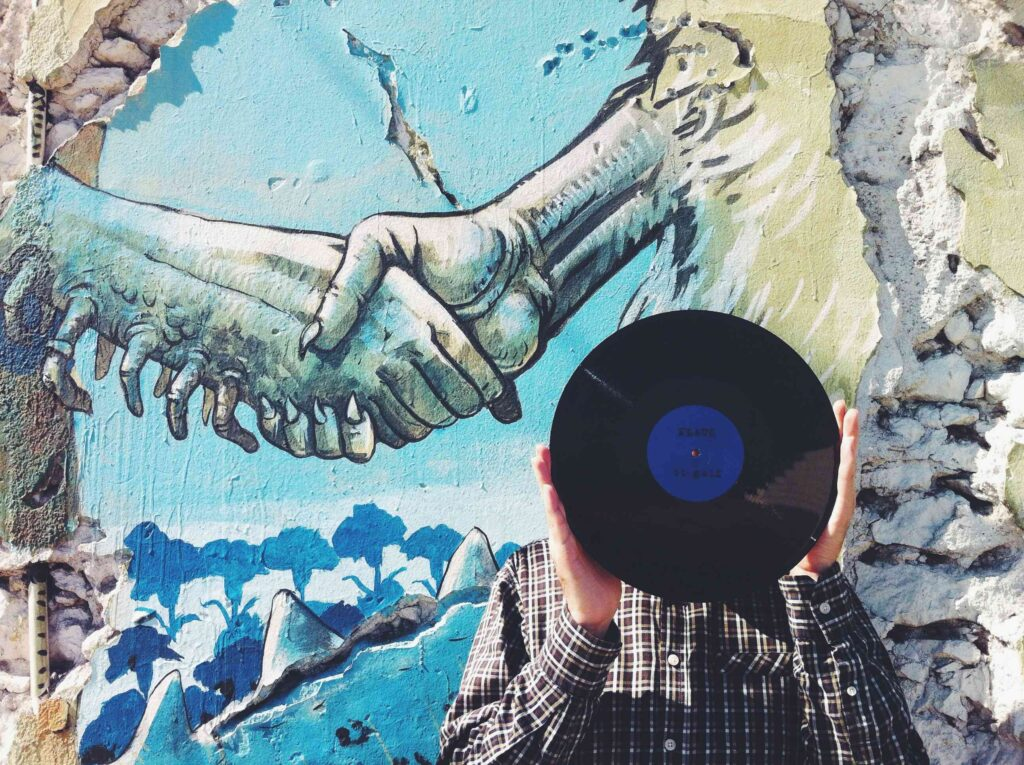 Artsy image of a man holding a vinyl record in front of a mural of two hands;An honest conversation about vinyl considers alternatives